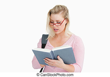 Serious woman reading a book while wearing glasses