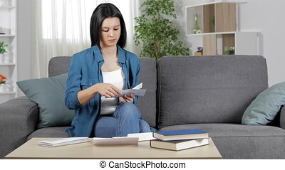 Serious woman reading a receipt at home - Serious woman...