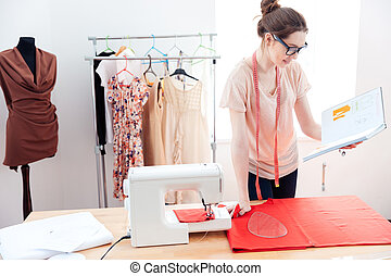 Serious woman seamstress working with red fabric in studio