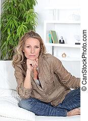 Serious woman sitting crossed legged on a white sofa