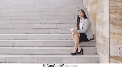 Serious woman sitting on stairs outdoors