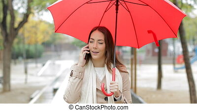 Serious woman talking on phone under the rain - Front view...