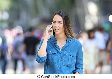 Serious woman talks on phone on the street