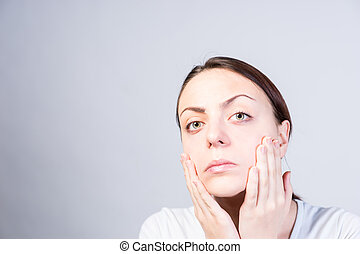 Serious Woman Touching her Face with Two Hands - Close up...