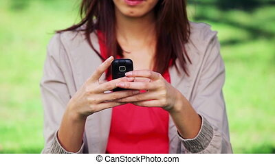 Serious woman typing on her cellphone