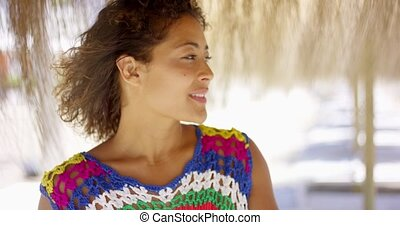 Serious woman under thatch beach umbrella - Beautiful...