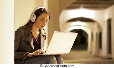 Serious woman using a laptop with headphones in the night