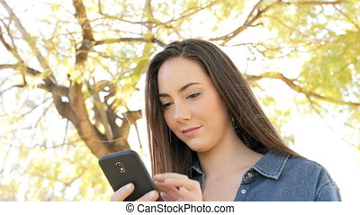Serious woman using smart phone in a park