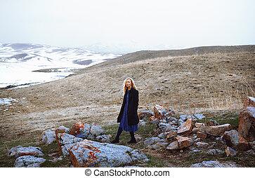 Serious woman walking in the winter landscape