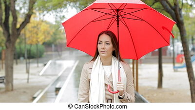 Serious woman walking under the rain in a park