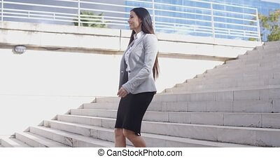 Serious woman walking up staircase - Serious young business...