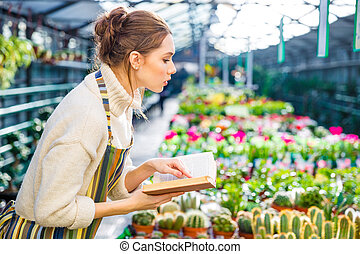 Serious woman with book working in garden center