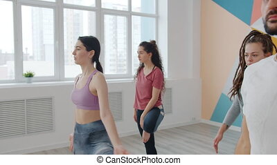 Serious young women and man in sportswear are enjoying relaxation during yoga practice in sports center balancing on one foot enjoying tree position.