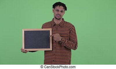 Serious young African man holding blackboard and giving ...