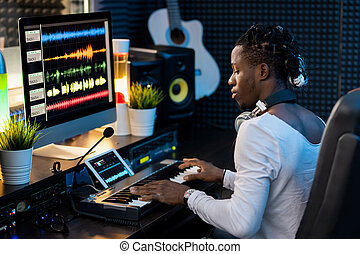 Serious young African man pressing keys of piano keyboard in...