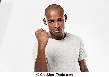 Serious young african man showing fist.