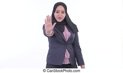 Serious young African Muslim businesswoman with stop gesture...