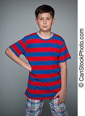 Serious young boy against the gray background