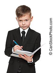 Serious young boy in black suit with a notebook