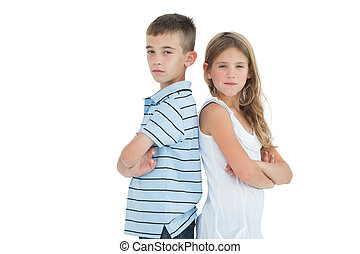Serious young brother and sister posing back to back