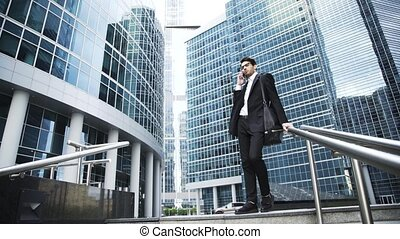 Serious young businessman in glasses talking on his phone in a downtown