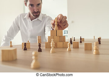 Serious young businessman positioning king chess piece on top of pyramid