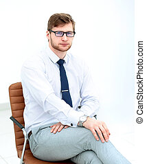 serious young businessman sitting in office chair.