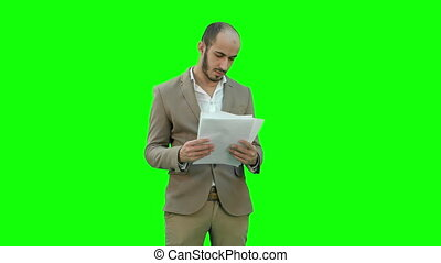 Serious young businessman standing and reading some documents on a Green Screen, Chroma Key.