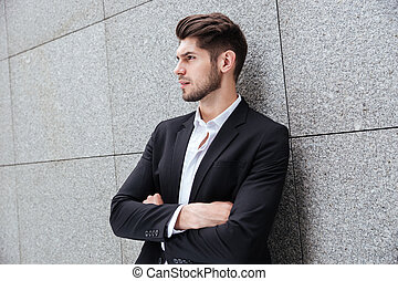 Serious young businessman standing with arms crossed