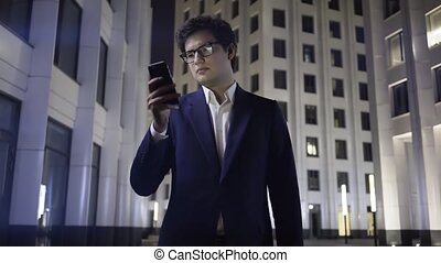 Serious young businessman web surfing in a night city