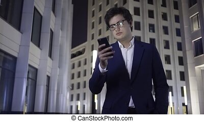 Serious young businessman with a smartphone and headphones walks in a night city