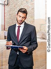 businessman writing on clipboard