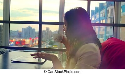Serious young businesswoman using tablet drinks tea  sitting in a restaurant with beautiful view from window on blurred city in lights and bokeh, lens flare. 4k