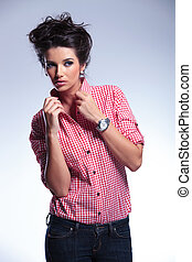 serious young casual woman pulling her collar
