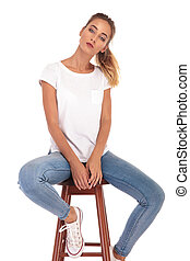 serious young casual woman sitting on a stool