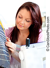 Serious young caucasian woman sewing in the kitchen