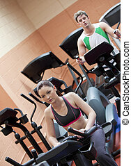 Serious young couple doing exercises using equipments in a sport centre