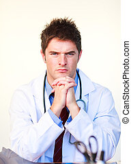 Serious young doctor looking at the camera