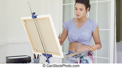 Serious young female artist painting outdoors on a patio...