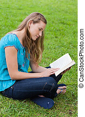 Serious young girl reading a book while sitting in a park