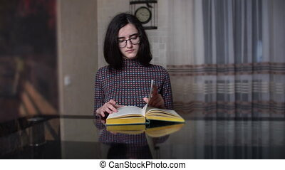 Serious young girl reads a book while sitting in the kitchen in the evening