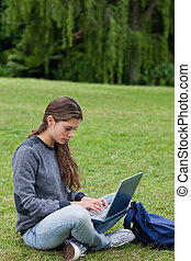 Serious young girl using her laptop while sitting...