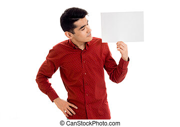 serious young guy in red t-shirt with empty placard in his hands isolated on white background