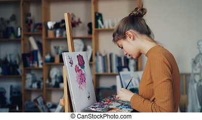 Serious young lady art student is painting flowers on canvas...