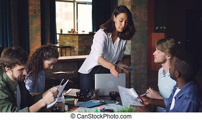 Serious young lady is giving documents to her employees who...