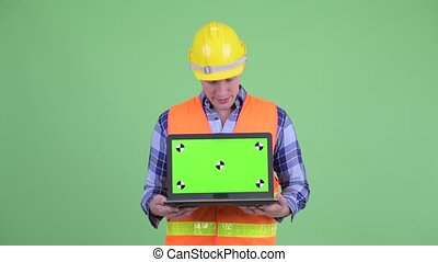 Serious young man construction worker showing laptop and...
