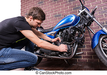 Serious Young Man Fixing his Blue Motorbike