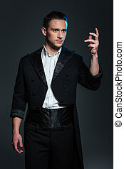 Serious young man magician in black tail coat showing tricks