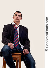 serious young man sitting on chair