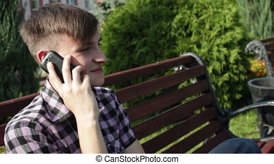 serious young man talking on the phone in park